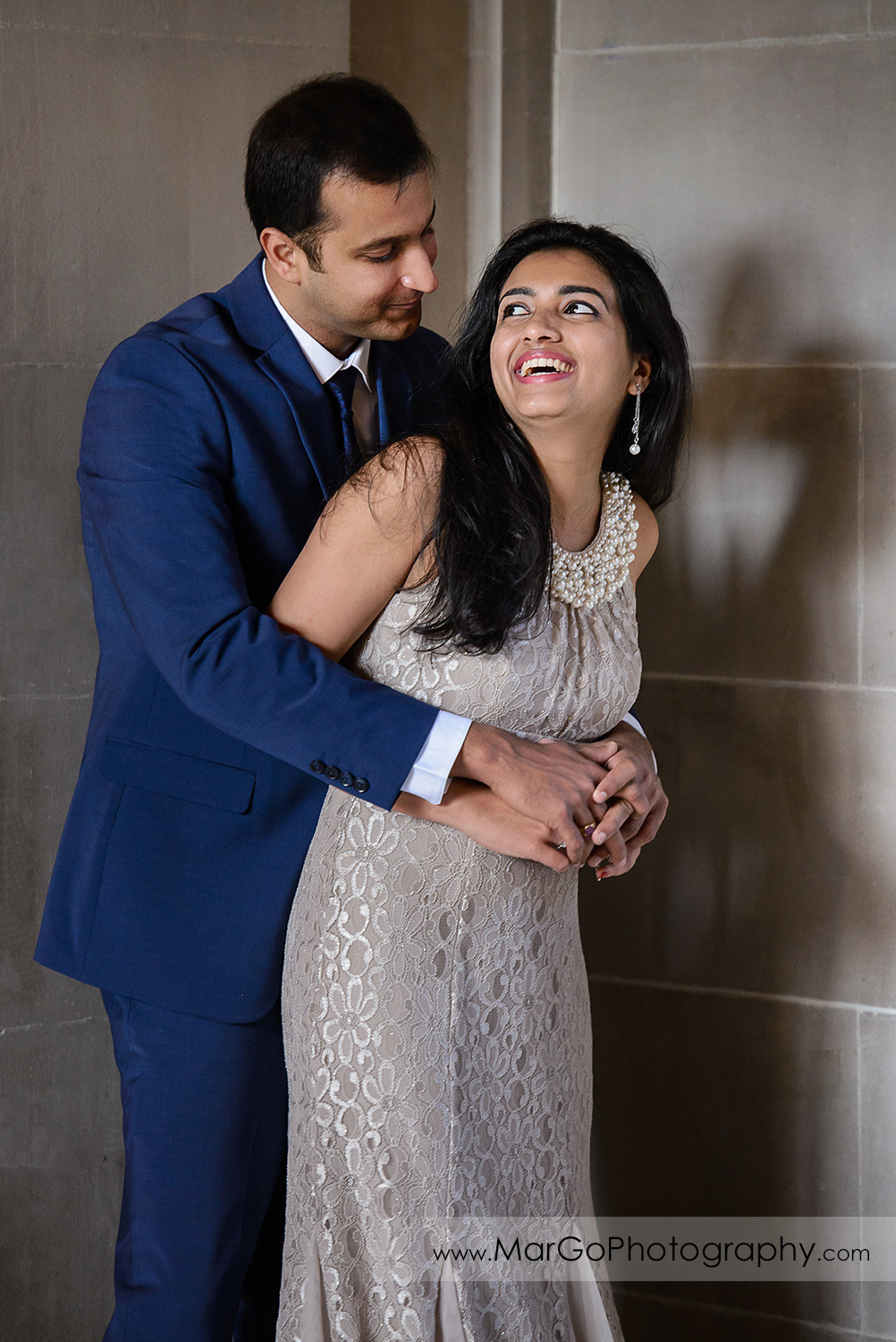 man in navy blue suit and woman in beige dress laughing on the third floor of San Francisco City Hall
