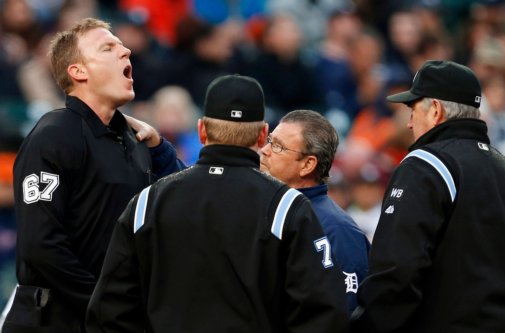 . Home plate umpire Seth Buckminster (67) reacts after being hit by a ball in the third inning of a baseball game between the Detroit Tigers and the Houston Astros in Detroit, Wednesday, May 7, 2014. (AP Photo/Paul Sancya)