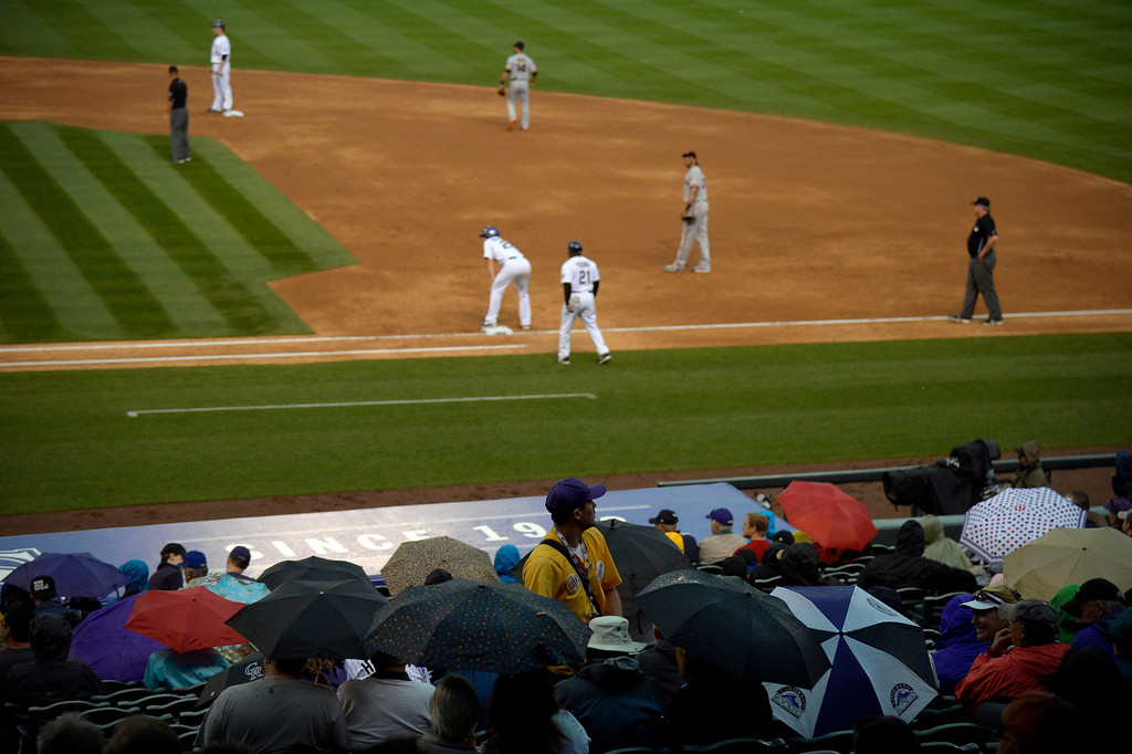 . DENVER, CO - MAY 22: Fans take out the umbrellas during the Colorado Rockies San Francisco game May 22, 2014 at Coors Field. Play was suspended due to rain and lightning in the area. (Photo by John Leyba/The Denver Post)