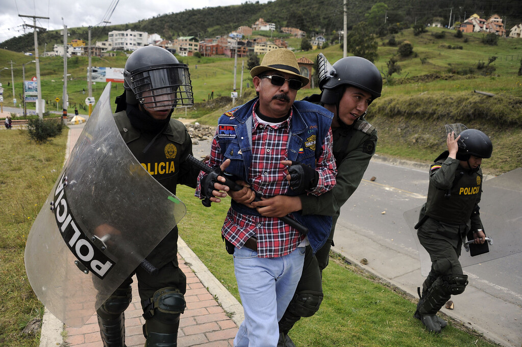 . Colombian police officers take a man into custody during a blockade set by farmers demanding government subsidies and greater access to land, in La Calera, Cundinamarca department, on August 23, 2013. A five-day-old farmworkers\' protest in Colombia claimed its first fatality Friday when a man on a motorcycle crashed and died at a roadblock, police said Friday. Since the protests began Monday, farmworkers have closed roads at dozens of points in across the country, blocking the passage of cargo trucks and other vehicles from makeshift camps erected on sides of roads. EITAN ABRAMOVICH/AFP/Getty Images