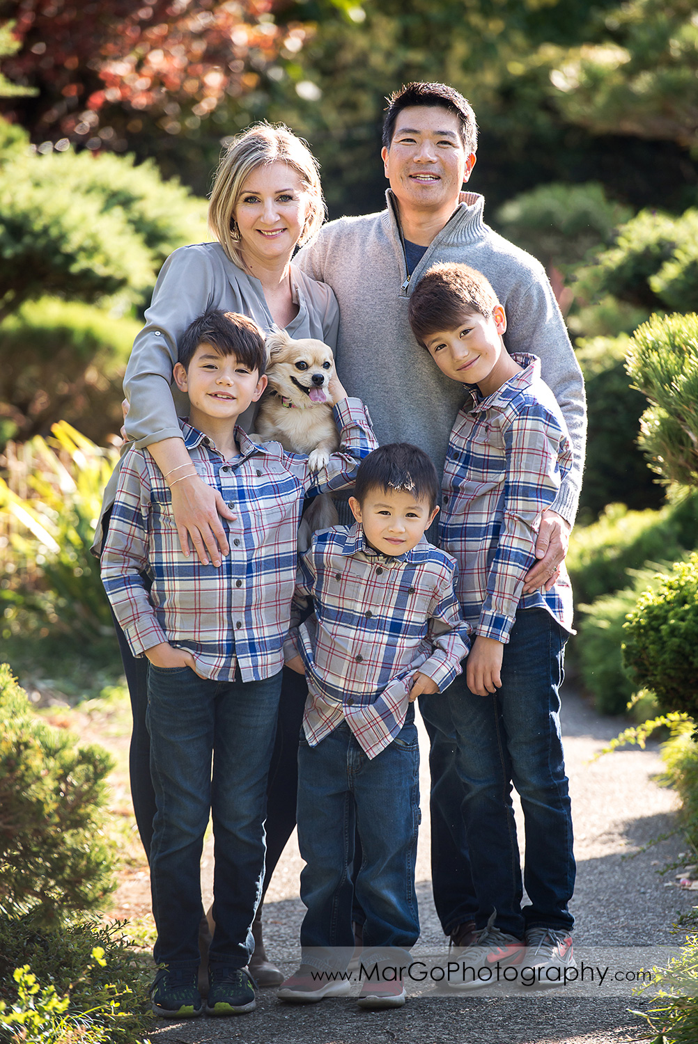 portrait of family of five in gray shirts and a dog looking into camera at Hayward Japanese Garden