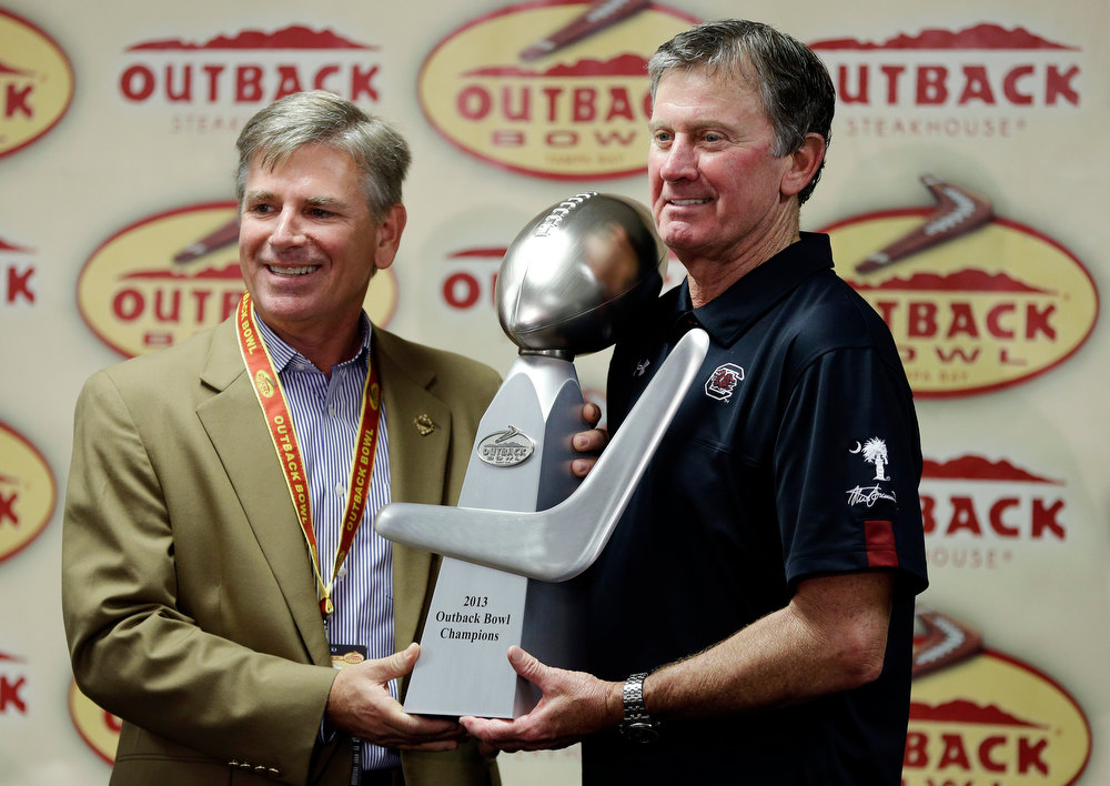 . South Carolina head coach Steve Spurrier, right, receives the trophy from committee member Chuck Johnson after their 33-28 win over Michigan in the Outback Bowl NCAA college football game, Tuesday, Jan. 1, 2013, in Tampa, Fla. (AP Photo/Chris O\'Meara)