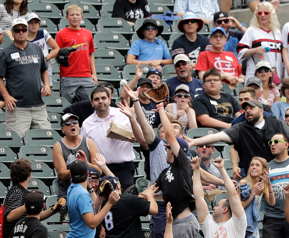 . Baseball fans go after Cleveland Indians\' Francisco Lindor\'s home run during the first inning of a baseball game against the Chicago White Sox Thursday, June 14, 2018, in Chicago. (AP Photo/Charles Rex Arbogast)