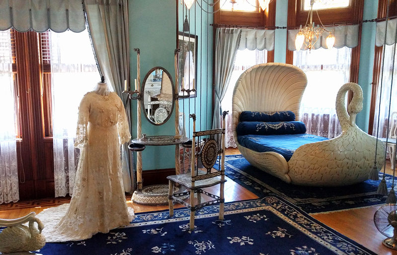 Sallie May Dooley's swan-shaped bed and a mannequin displaying a dress in Maymont Mansion.