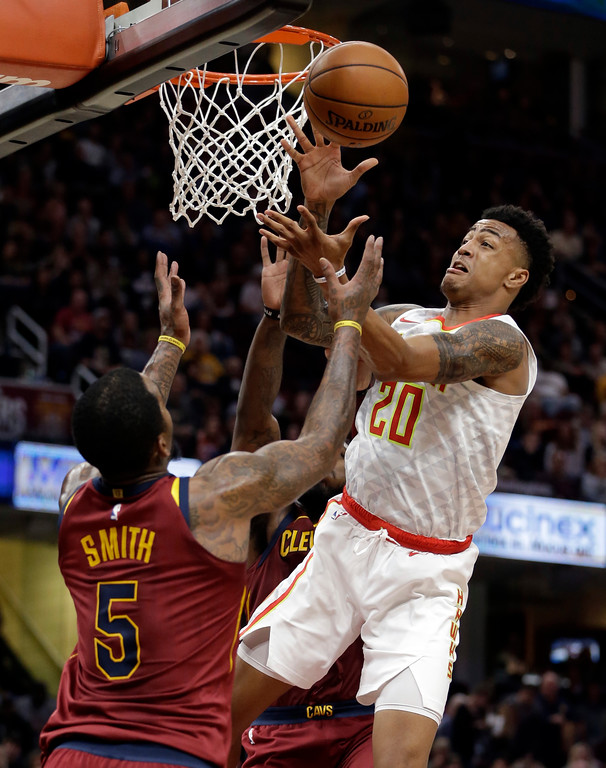 . Atlanta Hawks\' John Collins (20) and Cleveland Cavaliers\' JR Smith (5) battle for a rebound in the first half of an NBA basketball game, Sunday, Nov. 5, 2017, in Cleveland. (AP Photo/Tony Dejak)