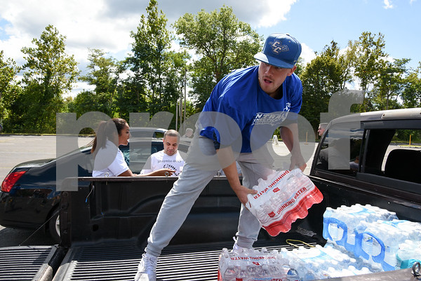 09/08/17 Wesley Bunnell | Staff A Pack the Truck event for Hurricane Harvey relief took place on Friday afternoon in the parking lot at New Britain Stadium. The event was a partnership between the New Britain Bees, Houston Astros outfielder George Springer, Siracusa Moving and Storage, A1 Automotive Repair, the Connecticut Blue Jays AAU Travel Team and Premier Limousine with trucks from Siracusa leaving for Houston following the event. CCSU Baseball student athlete Nick Garland stands in the truck to unload donations of bottled water from Elohim Casa De Dios of Meriden.