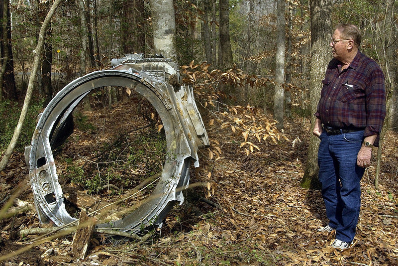 . Wink Miller looks at a piece of debris believed to be from the space shuttle Columbia he found in the trees near Hemphill, Texas, Sunday, Feb. 2, 2003. (AP Photo/Mark Zimmerman)