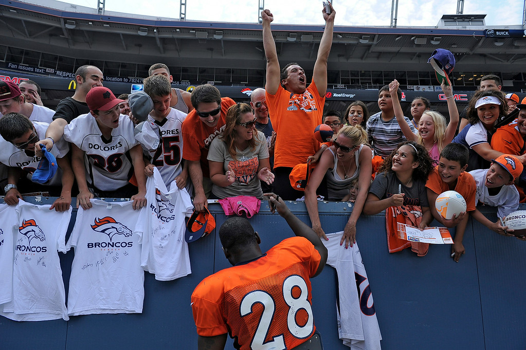 . Fans go crazy to have Denver Broncos running back Montee Ball (28) sign autographs after practice on day four of the Denver Broncos 2014 training camp July 27, 2014 at Sports Authority Field at Mile High. (Photo by John Leyba/The Denver Post)