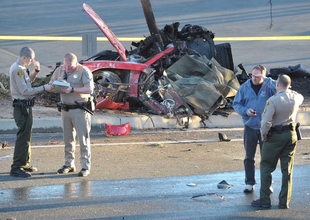 . Sheriff deputies work near the wreckage of a Porsche sports car that crashed into a light pole on Hercules Street near Kelly Johnson Parkway in Valencia on Saturday, Nov. 30, 2013.  (AP Photo/The Santa Clarita Valley Signal, Dan Watson)