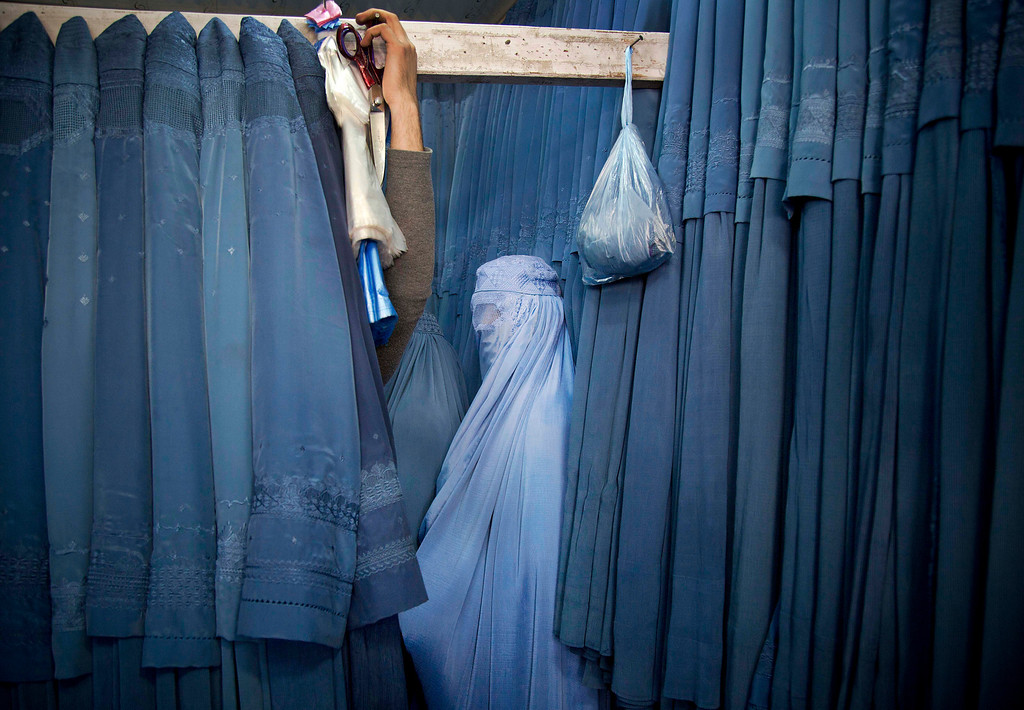 . In this Thursday, April 11, 2013 file photo made by Associated Press photographer Anja Niedringhaus, an Afghan woman waits in a changing room to try out a new Burqa, in a shop at in the old city of Kabul, Afghanistan. (AP Photo/Anja Niedringhaus, File)