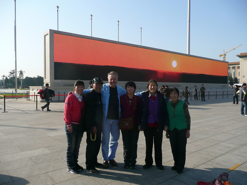 friendly Family, backdrop is one of two massive Video Screens in Tian'anmen Square,  Beijing,  2010