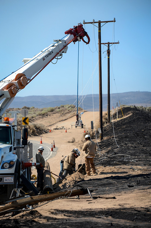 . Edison workers begin to repair damaged power lines along Lancaster road which were burned in the Power House fire.   Photo by David Crane/Los Angeles Daily News