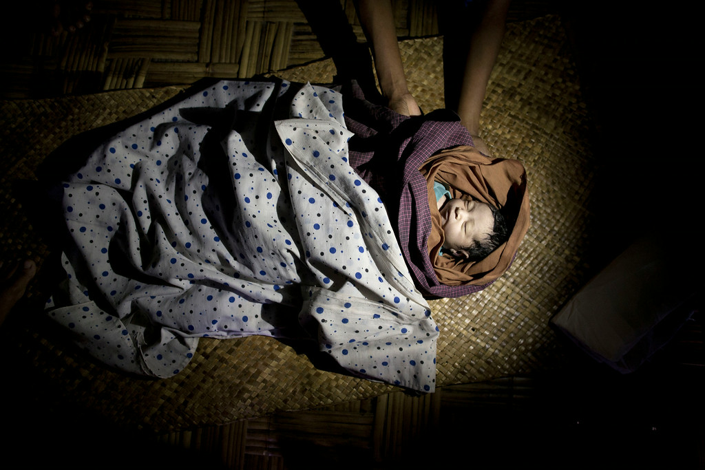 . In this June 27, 2014 photo, the hands of Hasina reach down to hold her grand daughter\'s tiny corpse in Dar Paing, a camp for Rohingya refugees in north of Sittwe, Rakhine state, Myanmar. The baby girl died and was buried just hours after she was born, another victim of a humanitarian crisis that is gripping western Myanmar. The family is among 140,000 Rohingya Muslims living in camps outside of Sittwe after rampaging Buddhist mobs chased them from their homes in 2012. (AP Photo/Gemunu Amarasinghe)