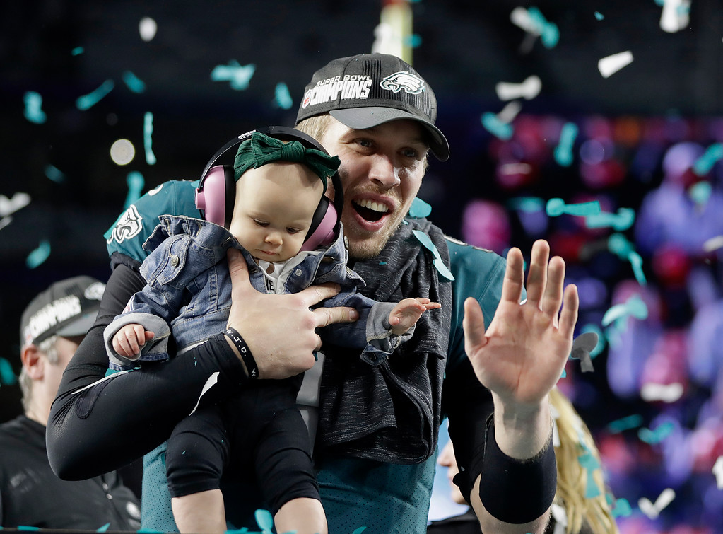 . Philadelphia Eagles\' Nick Foles holds up his daughter, Lily, after the NFL Super Bowl 52 football game against the New England Patriots, Sunday, Feb. 4, 2018, in Minneapolis. The Eagles won 41-33. (AP Photo/Mark Humphrey)