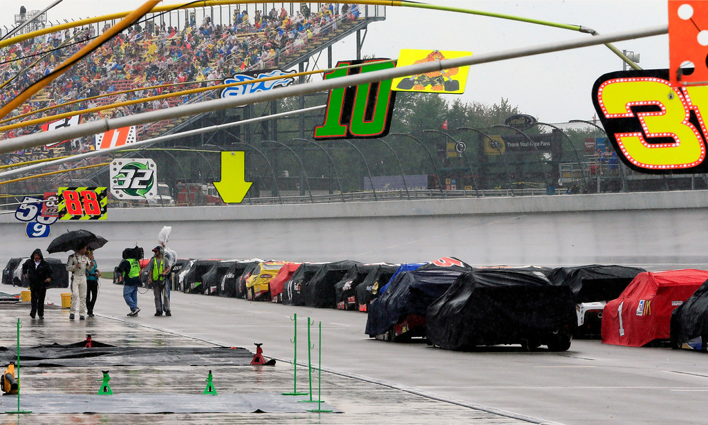 . NASCAR Sprint Cup series auto race cars are parked on pit row during a rain delay at Michigan International Speedway, Sunday, June 14, 2015, in Brooklyn, Mich. (AP Photo/Carlos Osorio)