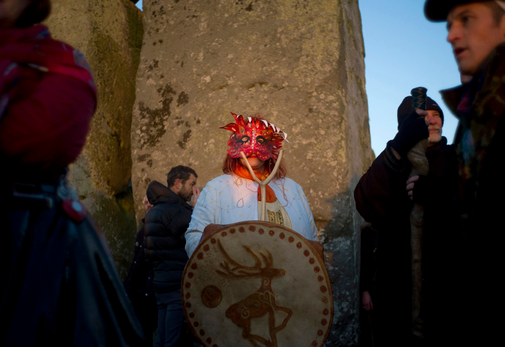 Description of . A reveller watches the sunrise during the winter solstice at Stonehenge on Salisbury Plain in southern England December 21, 2012. The winter solstice is the shortest day of the year, and the longest night of the year. REUTERS/Kieran Doherty