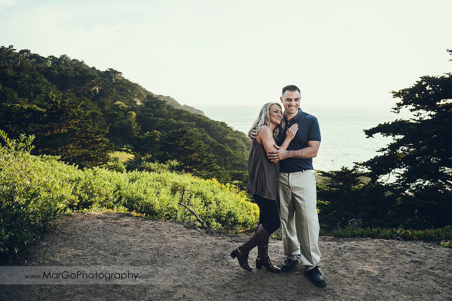 man in navy blue shirt and woman in brown tunic holiding on the trail during engagement session at San Francisco Lands End