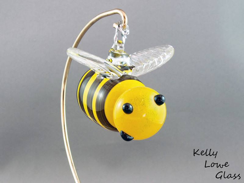 """Hanging Glass Bee:  A seasonal favorite, or a feared adversary, the bee can be either depending on the individual. But where would we be without them? Less flowers, no honey and 54% less buzzing in the world... would you REALLY want that?  Some of these bees even come with crowns, showing off their royal status as queen bees.  Stinger to Nose: Approx 9cm (3.54"""") Across the Wings: Approx 6cm (2.36"""") Weight: Approx 150g (0.33 lbs)  Click here to see more of this bee, with measurements, and other glass insects (Link opens in a new window)"""