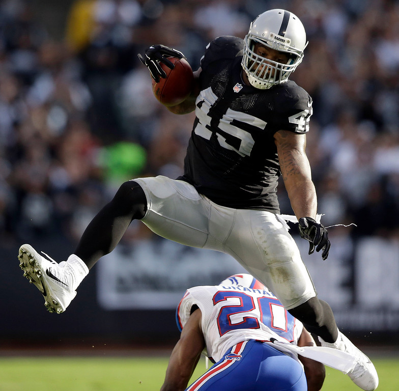 . Oakland Raiders fullback Marcel Reece (45) jumps over Buffalo Bills cornerback Corey Graham (20) during the second quarter of an NFL football game in Oakland, Calif., Sunday, Dec. 21, 2014. (AP Photo/Marcio Jose Sanchez)