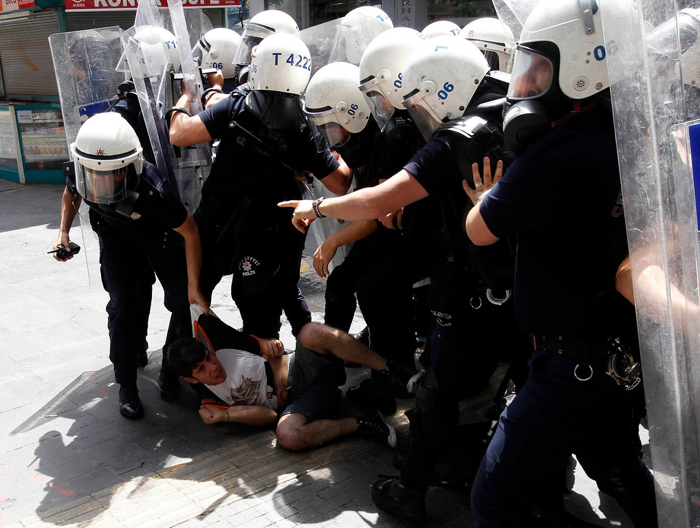 . Riot police surround a protester during a protest against Turkey\'s Prime Minister Tayyip Erdogan and his government\'s policy on Syria, in Ankara May 18, 2013. Erdogan said on Friday it would be up to the U.N. Security Council to decide whether to establish a no-fly zone inside Syria and said he backed the involvement of Russia and China in planned peace talks.      REUTERS/Umit Bektas