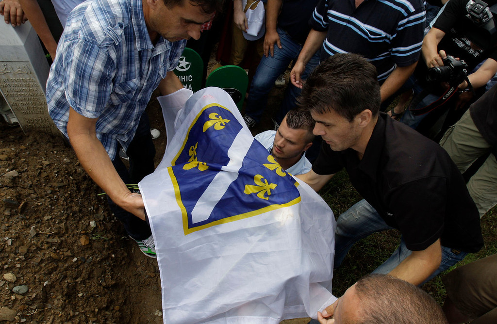. Bosnian men carry the small coffin of Hava Muhic\'s baby during a mass funeral for Srebrenica victims in memorial center Potocari, near Srebrenica, 160 kms east of Sarajevo, Bosnia, on Thursday, July 11, 2013. Hava Muhic believes she should be baking a cake, with her husband and calling friends and family for the party. Instead, Muhic stood above the smallest pit in the cemetery, near her husband\'s grave which was dug for her baby girl who died here 18 years ago on the day of the worst massacre Europe has seen since World War II. Muhic\'s baby is among 409 newly identified victims of the Srebrenica massacre buried on Thursday in an annual mass funeral at the Potocari Memorial Center on the July 11 anniversary. This year\'s commemorations bring the total of identified victims to 6,066. Another 2,306 remain missing.  (AP Photo/Amel Emric)