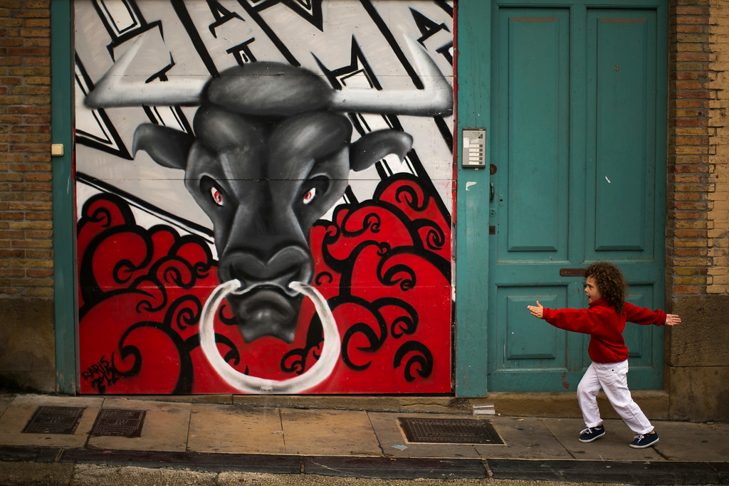 """. A young reveler dressed in a traditional outfit runs next to a mural of a bull during the opening day of the 2014 San Fermin fiestas in Pamplona, Spain, Sunday, July 6, 2014. Revelers from around the world turned out to kick off the festival with a messy party in the Pamplona town square, one day before the first of eight days of the running of the bulls glorified by Ernest Hemingway\'s 1926 novel \""""The Sun Also Rises.\"""" (AP Photo/Andres Kudacki)"""