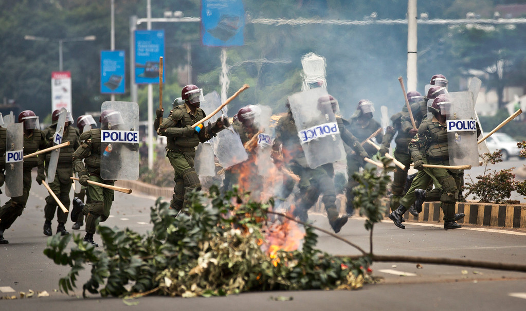 . Riot police charge past a burning barricade as they engage in running battles with protesting Kenyan students on the highway next to Nairobi University\'s main campus in downtown Nairobi, Kenya Tuesday, May 20, 2014. Kenyan university students on Tuesday carried out demonstrations over a proposed increase in student fees, but the protests quickly turned into hours of running battles between students throwing rocks and security forces firing tear gas, before riot police chased the students inside their campus and cornered them in a building into which they fired dozens of tear gas grenades and for a while prevented anyone from leaving. (AP Photo/Ben Curtis)