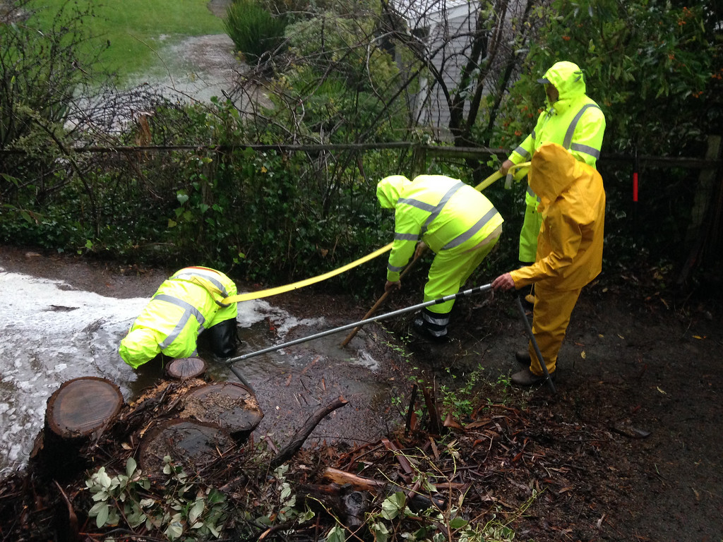 . A Tiburon Publics Works crew clears a drain behind Harn Court in Tiburon, Calif., on Thursday, Dec. 11, 2014. (Frankie Frost - Marin Independent Journal)