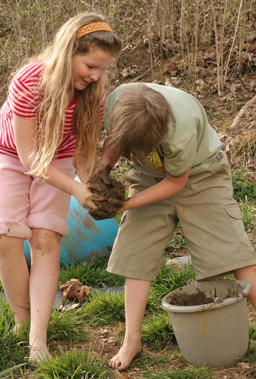 """The kids put the mud from the hill into a bucket, then squished it and poured it out at the top of the hill, letting it roll down, picking up dry dirt, making """"meat loaf""""."""