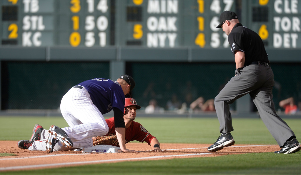 . Arizona Diamondbacks right fielder Gerardo Parra (8) looks up a 1B umpire Mike Estabrook for the call as he gets tagged out by Colorado Rockies first baseman Justin Morneau (33) in the third inning June 4, 2014 at Coors Field. (Photo by John Leyba/The Denver Post)