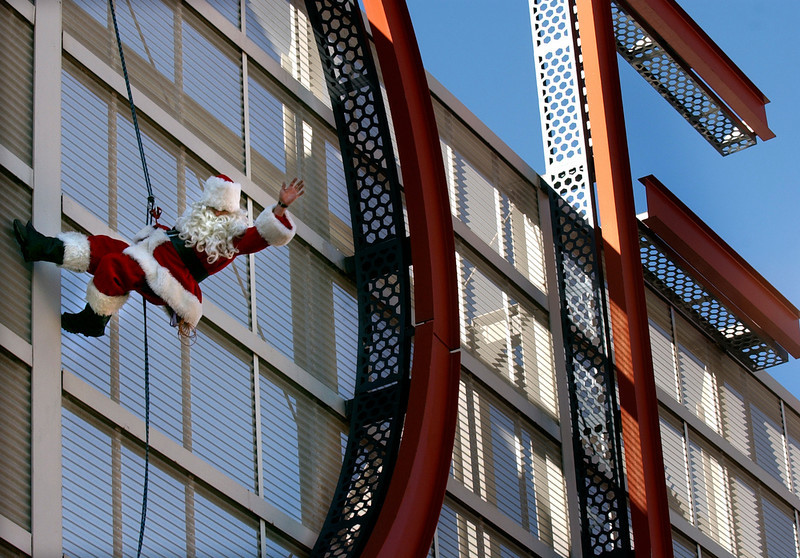 """. Santa Claus rappels the letter \""""D\"""" in the landmark DENVER sign at the Denver Pavilions in downtwon Denver to let folks know he is getting ready for the holidays. The marquee is 147 feet wide and 35 feet, 6 inches high at its highest point. Each letter in the word \""""Denver\"""" weighs 3,000 pounds. DENVER POST / KATHRYN SCOTT OSLER"""