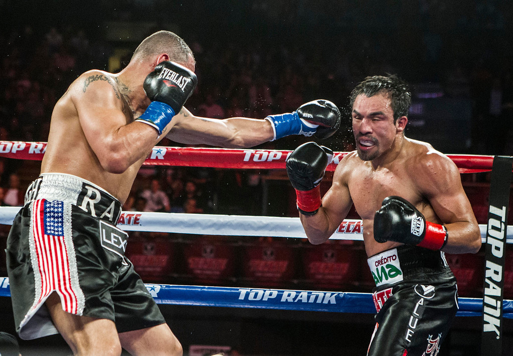 . Mike Alvarado, left, lands a punch to the face of Juan Manuel Márquez, of Mexico, exchange punches in the fifth round of a WBO welterweight title boxing match at the Forum in Inglewood, Calif., Saturday, May 17, 2014. Márquez won the title.  (AP Photo/Ringo H.W. Chiu)
