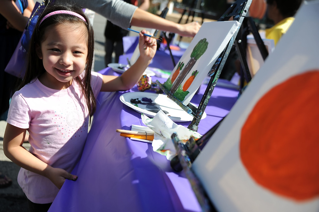 . Five year-old Makayla Gatmaitan of Altadena smiles as she paints during the 8th Annual Pasadena ARTWalk along El Molino Avenue between Colorado Boulevard and Green Street in Pasadena, Calif., on Saturday, Oct. 12, 2013. The ArtWalk features over 30 participating artists, art sales, gallery walks, musical performances and other activities.   (Keith Birmingham Pasadena Star-News)