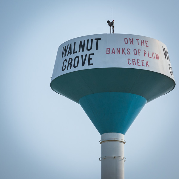 A water tower in large letters reads 'Walnut Grove' on one side, and in small letters reads, 'On the Banks of Plum Creek' on the other side.