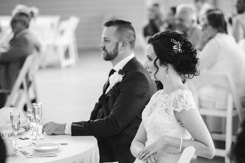 The profile of the bride and groom as they smile, watching the speech.