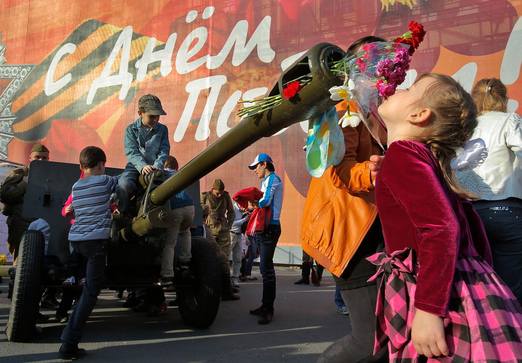 . A girl smells the flowers insert?d to the barrel of an artillery canon during celebration of the Victory Day in St.Petersburg, Russia, Thursday, May 9, 2013. Russia is celebrating the anniversary of victory over Germany in WWII. The poster reads: \' Congratulation with Victory Day!\'. (AP Photo/Dmitry Lovetsky)
