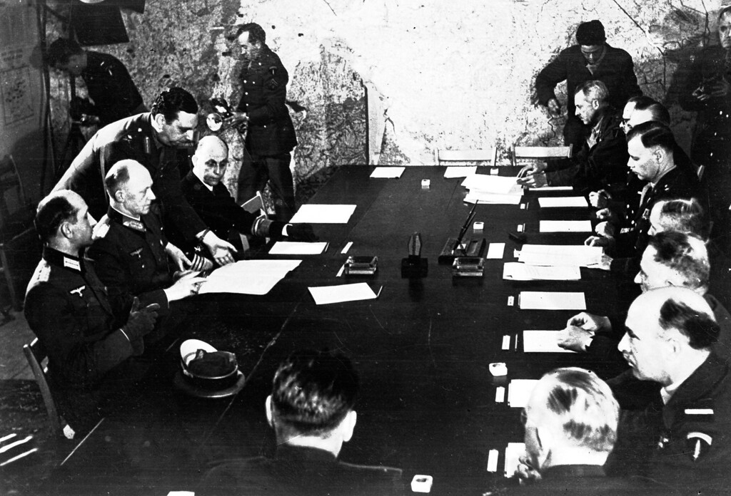 . German delegates, left, agree an unconditional surrender with Allied representatives, right, in an upstairs room at SHAEF, formerly the College Moderne de Garcons, in Reims, France, May 7, 1945. The German delegates, from left, are: Maj. Wilhelm Oxenius, an aide to Gen. Jodl; Gen. Alfred Jodl; and Adm. Hans-Georg von Friedeburg. Standing behind them is SHAEF\'s Gen. K. Strong. The Allied  representatives, from the far end of the table, are: SHAEF\'s Gen. Morgan; France\'s Gen. Francois Sevez; Adm. Burrough; SHAEF\'s Gen. Walter Bedell Smith; Russia\'s Gen. Ivan Suslaparov; U. S. Gen. Carl Spaatz; SHAEF\'s Air Marshal Robb; SHAEF\'s Maj. Gen. Harold R. Bull; and Russia\'s Col. Zenkovitch. (AP Photo/Morse)