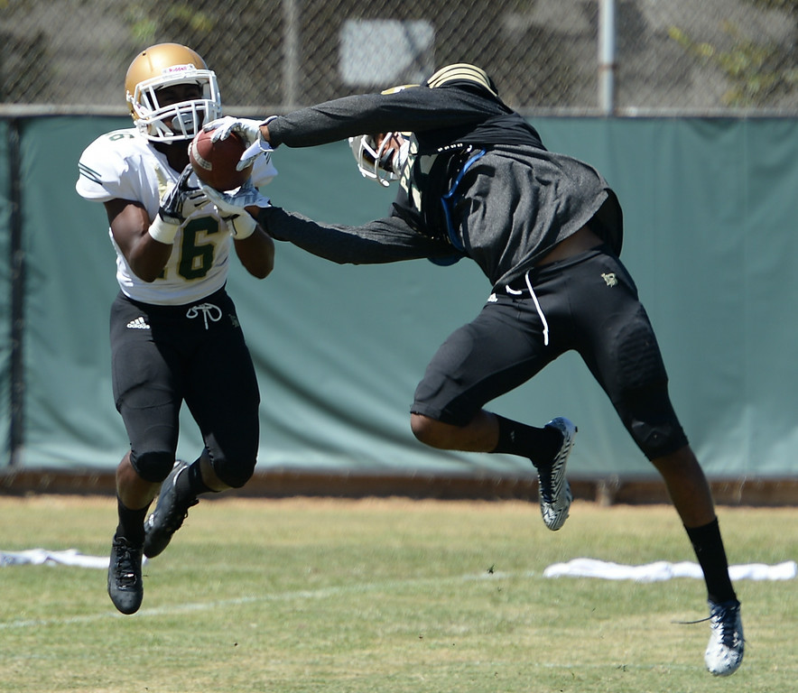 ". All American defensive back Iman ""Biggie\"" Marshall, right, intercepts a pass during drills at Long Beach Poly football practice Saturday, August 16, 2014, Long Beach, CA.   Photo by Steve McCrank/Daily Breeze"