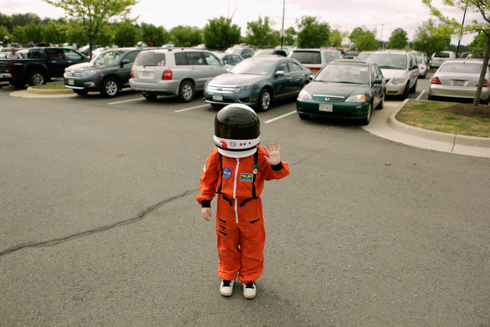 Description of . A young boy wears an astronaut costume in the parking lot of the Smithsonian National Air and Space Museum Steven F. Udvar-Hazy Center April 17, 2012 in Chantilly, Virginia. Hundreds of people gathered at the museum early in the morning to watch the arrival of the space shuttle Discovery, teathered to the back of a modified 747 jumbo jet. The oldest and most traveled vehicle in NASA's space shuttle program, Discovery will be placed on permanent display at the museum.  (Photo by Chip Somodevilla/Getty Images)