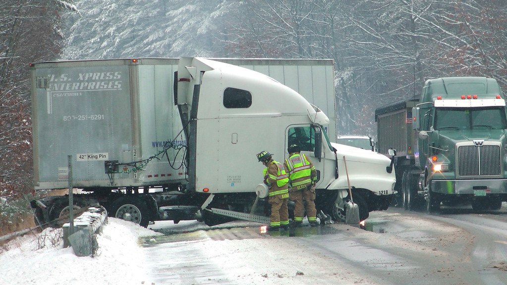 . Firefighters tend to a tractor trailer that went off the road on Interstate 89 North in Hopkinton, N.H., Monday, Dec. 12, 2016. State police said the truck struck a guardrail and leaked gallons of fuel onto the road. No one was injured. The driver was cited for driving too fast for the road conditions and for a commercial vehicle logbook violation. (AP Photo/Holly Ramer)