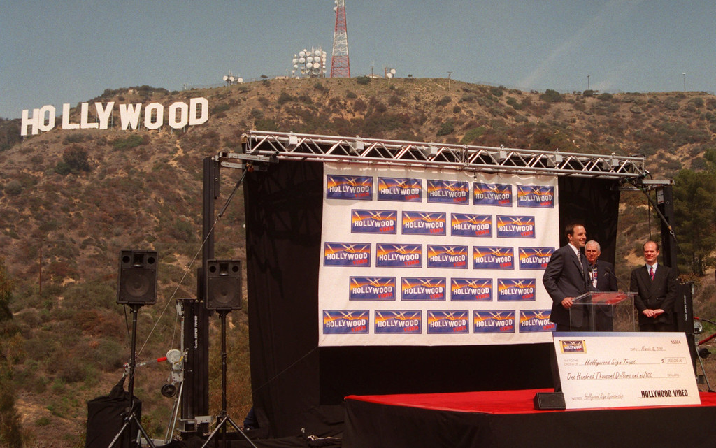 . Mark Wattles, CEO of Hollywood Video, left, talks to the media after presenting Ed McMahon, center, and Chris Baumgardt, president of the Hollywood Sign Trust a check for $100,000 for the adoption of the Hollywood sign for one-year, during a cermony Thursday, March 18, 1999, in the Hollywood section of Los Angeles. The money will provide painting, repairs and general maintenance to the world-famous hilltop sign, erected in 1923 and originally intended to stand for only 18 months ( AP Photo/Michael Tweed)
