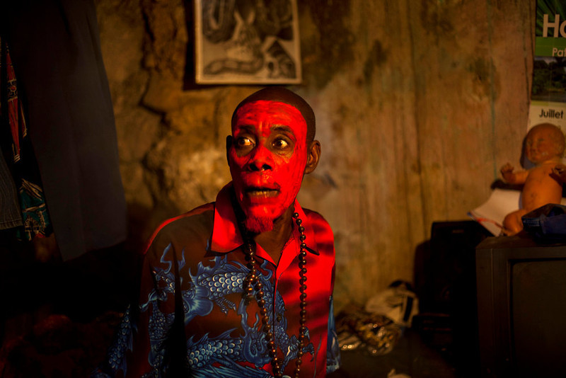 . In this Jan. 27, 2013 photo, snake handler Saintilus Resilus, with his face painted red, talks to his assistants as they get ready to perform during pre-Lenten Carnival season in Petionville, Haiti. Resilus sees himself as something of a performance artist, showing off with snakes and other animals that Haitians don\'t see every day, earning tips from impromptu audiences. (AP Photo/Dieu Nalio Chery)