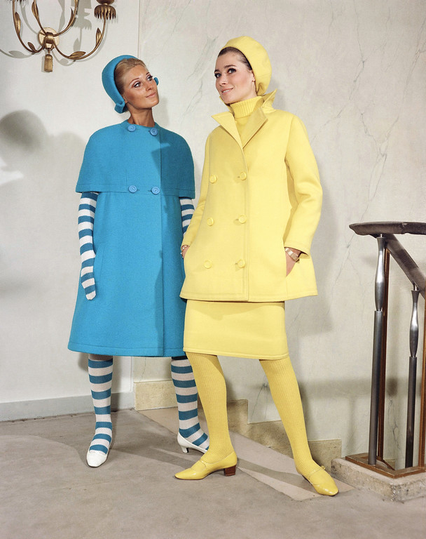 . At left ?Gaspard? a dark blue woolen coat worn with a matching hat and with blue and white rays? woolen gloves and stockings plus white leather shoes. At right ?Thomas?, a yellow woolen ensemble (skirt, long jacket and beret hat) worn over a pullover and matching woolen stockings plus yellow leather shoes. Both dresses were featured at Jacque Heim?s fall winter collection, August 27, 1966. (AP Photo)