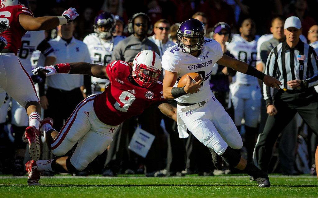 . Quarterback Kain Colter #2 of the Northwestern Wildcats slips past defensive end Jason Ankrah #9 of the Nebraska Cornhuskers during their game at Memorial Stadium on November 2, 2013 in Lincoln, Nebraska. (Photo by Eric Francis/Getty Images)