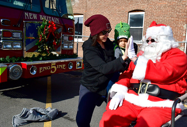 12/1/2018 Mike Orazzi | Staff Stacy Rosado and her son John Franco Rosado,2, meet with Santa during a fill a fire truck event at the New Britain Elks Lodge No. 957 with help from the New Britain Fire Department Saturday morning in New Britain. Items collected are to benefit the disabled veterans of New Britain and Newington.