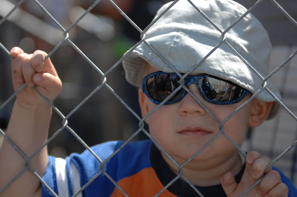 . 04/20/13 - Rhys Stallcup, 2-years, watches the qualifying rounds through the fence at the 39th Annual Toyota Grand Prix of Long Beach. Photo by Brittany Murray / Staff Photographer