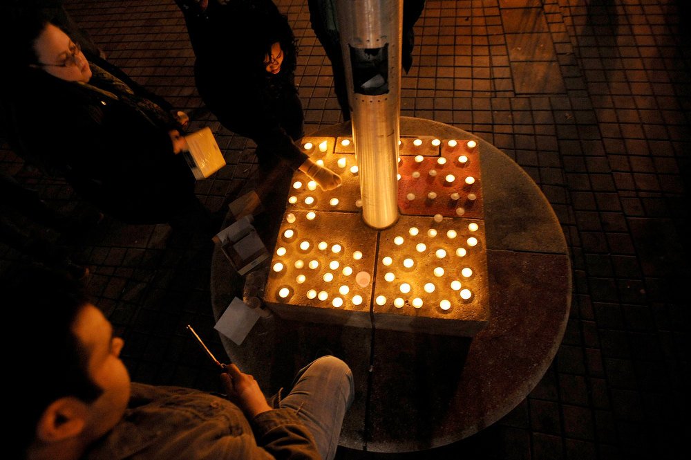 Description of . A woman lights candles during a vigil commemorating victims of a Connecticut elementary school shooting in Oakland, California, December 14, 2012. Twenty schoolchildren were slaughtered by a heavily armed gunman who opened fire at a suburban elementary school in Connecticut on Friday, ultimately killing at least 27 people including himself in the one of the worst mass shootings in U.S. History. The 20-year-old gunman, identified by law enforcement sources as Adam Lanza, fired what witnesses described as dozens of shots at Sandy Hook Elementary School in Newtown, Connecticut, which serves children from ages 5 to 10. REUTERS/Noah Berger