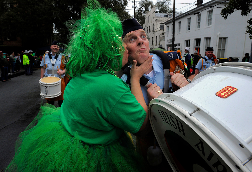 . Carolyn Geis, right, kisses Irish Air Corps Pipe and Drum member Terry Healy on the cheek during Savannah\'s 190-year-old St. Patrick\'s Day parade, Monday, March 17,  2014, in Savannah, Ga. Kissing men in uniform is a tradition during the celebration in Georgia\'s first city.  (AP Photo/Stephen B. Morton)