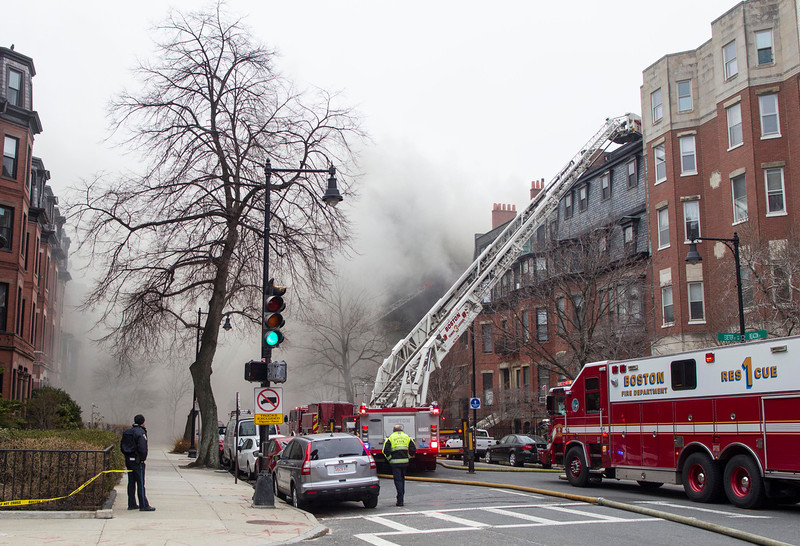 . Firefighters fight a multi-alarm fire at a four-story brownstone in the Back Bay neighborhood near the Charles River, Wednesday, March 26, 2014, in Boston. Boston EMS spokesman Nick Martin says four people, including at least three firefighters, have been taken to hospitals. (AP Photo/Scott Eisen)