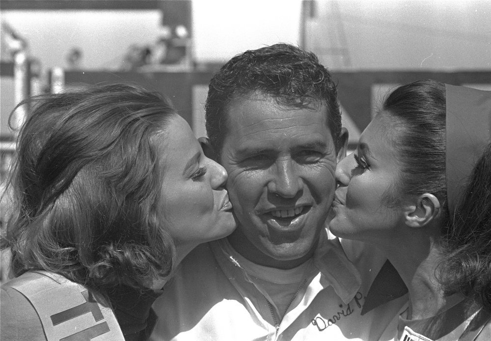 Description of . After winning the first 125-mile qualifying race at the Daytona International Speedway, February 20, 1969.  David Pearson is kissed from both sides in Victory Lane.  (AP Photo)